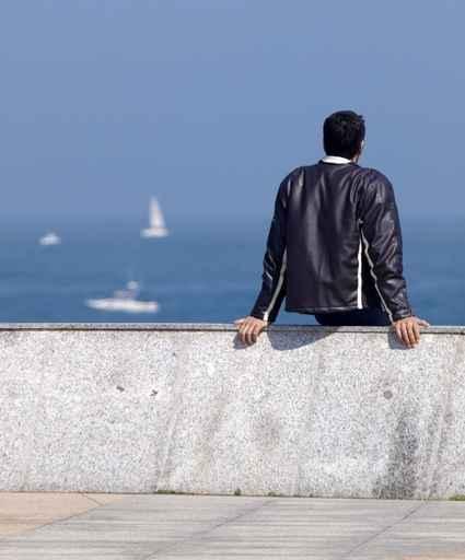 Joven sentado frente al mar